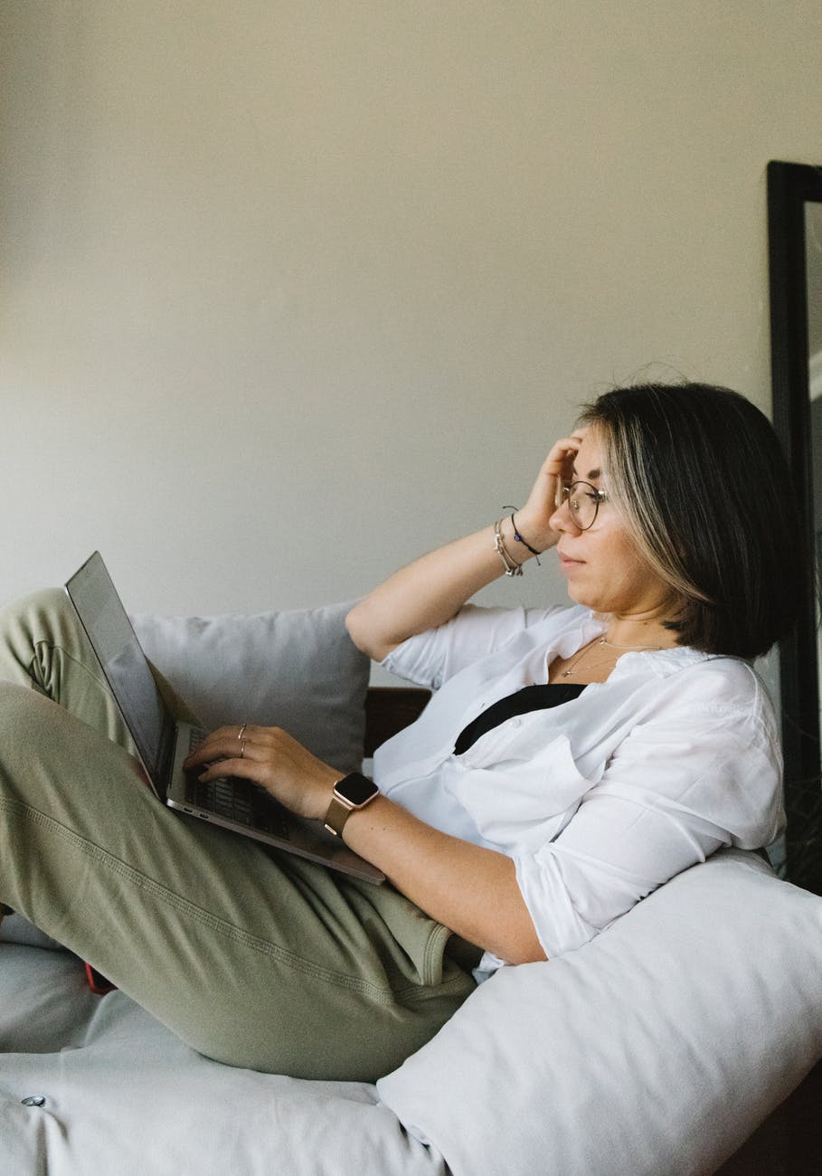 focused female freelancer working distantly on laptop sitting on couch