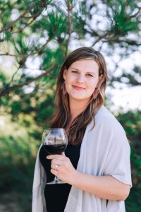 woman standing outside with a glass of wine
